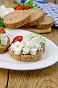 Bread with feta cheese and tomatoes on the board Stock Photos