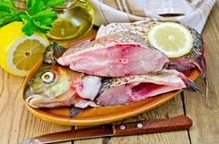 bream raw in a clay plate with a lemon on the board - stock photo