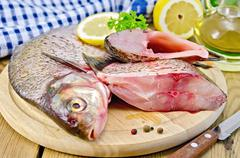 bream raw on a round board with a knife and oil - stock photo