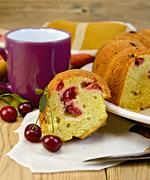 Cake with berries cherries and mug on the board Stock Photos