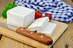 Stock Photo of feta cheese on a board with a knife and tomato