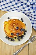 Flapjacks with blueberries and a fork on a board Stock Photos