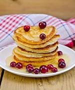 flapjacks with cranberries and honey on the board - stock photo