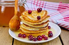 flapjacks with cranberry and spoon on board - stock photo