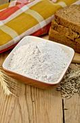 Flour rye in a bowl with bread and ears rye Stock Photos