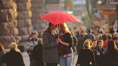 The lovers with heart-like umbrella above the people crowd, REAL TIME Stock Footage