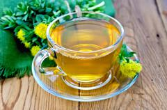 Herbal tea in a cup with a bouquet of rhodiola rosea on the board Stock Photos