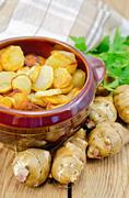 jerusalem artichokes roasted in a clay pot on a board - stock photo