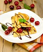 Pancakes with cherry and chocolate syrup with a napkin Stock Photos