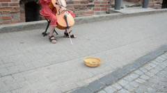 Girl play with violoncello in oldtown. wicker dish money Stock Footage