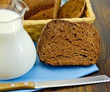 rye homemade bread with milk and a knife on a board - stock photo