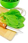 spinach on the board with a bowl - stock photo