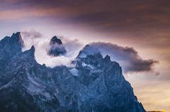 Stock Photo of cloudy mountain peaks at sunset
