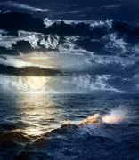 Stormy sea at night with dramatic sky and the big moon Stock Photos