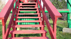 Going up in the red stairs found in the middle of the open greeny area Stock Footage