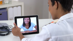 African American woman video chatting with doctor on ipad Stock Footage