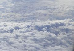 Fluffy white clouds from airplane window Stock Photos
