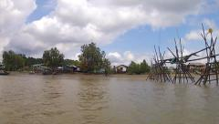 Boating through a rural fishing village in Sarawak, Malaysia (Borneo). Stock Footage
