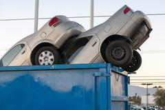 Junk cars in dumpster cash for clunkers Stock Photos