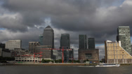 Stock Video Footage of London Skyline Canary Wharf Office Skyscraper Boat Passing Storm Clouds Rain Day