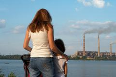 care future concept. young mother with her kids are looking at the chimney-stalk - stock photo