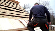 Stock Video Footage of roofer nailing the wooden roof tiles on the cedar wooden shingle shake ro