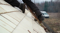 891 roofer using a ladder to get to the cedar wooden shingle shake roof Stock Footage