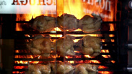 Roasted chickens on flamesover the glass window Stock Footage