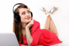 Stock Photo of cute girl with headphones and laptop lying