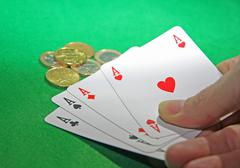 Hand with poker of aces on a table game Stock Photos