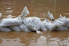 sandbags for flood defense and brown water - stock photo