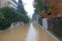 narrow road flooded during a downpour in the city - stock photo