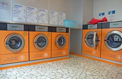 automatic washing machines in a laundromat - stock photo