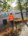 Stock Photo of street sweeper with orange jacket while blowing the dried leaves