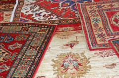 Collection of antique oriental carpets expensive on display in the boutique Stock Photos