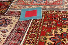 Blue carpet with red frame and other valuable oriental carpets Stock Photos