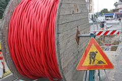 Roadworks and a coil of wire with the road sign Stock Photos
