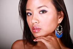 closeup portrait of a young beautiful asian model with makeup and jewelry - stock photo