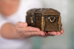 woman holding a locked antique chest in her hands - stock photo