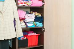 Various color clothes are organized at shelves in open wardrobe Stock Photos