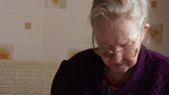 Stock Video Footage of elderly woman versed in documents