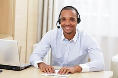 Stock Photo of young african american call center consultant with headset in office
