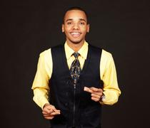 Young happy dancing african-american businessman on dark background Stock Photos