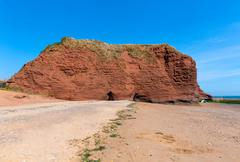 Red rock beach Dawlish Warren Devon England with blue sea - stock photo