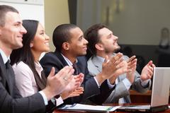 Multi ethnic business group greets somebody with clapping and smiling. focus  Stock Photos