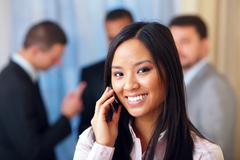 Portrait of young happy asian woman on phone with her business partners on th Stock Photos