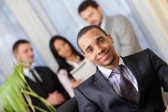 happy african-american businessman with his team working behind - stock photo