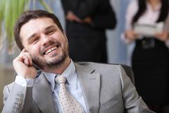 laughing executive businessman on the phone while his team is working behind - stock photo