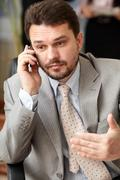 portrait of a mature business man screaming in his cellphone in office enviro - stock photo