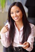 Portrait of a young beautiful asian woman in a business environment Stock Photos